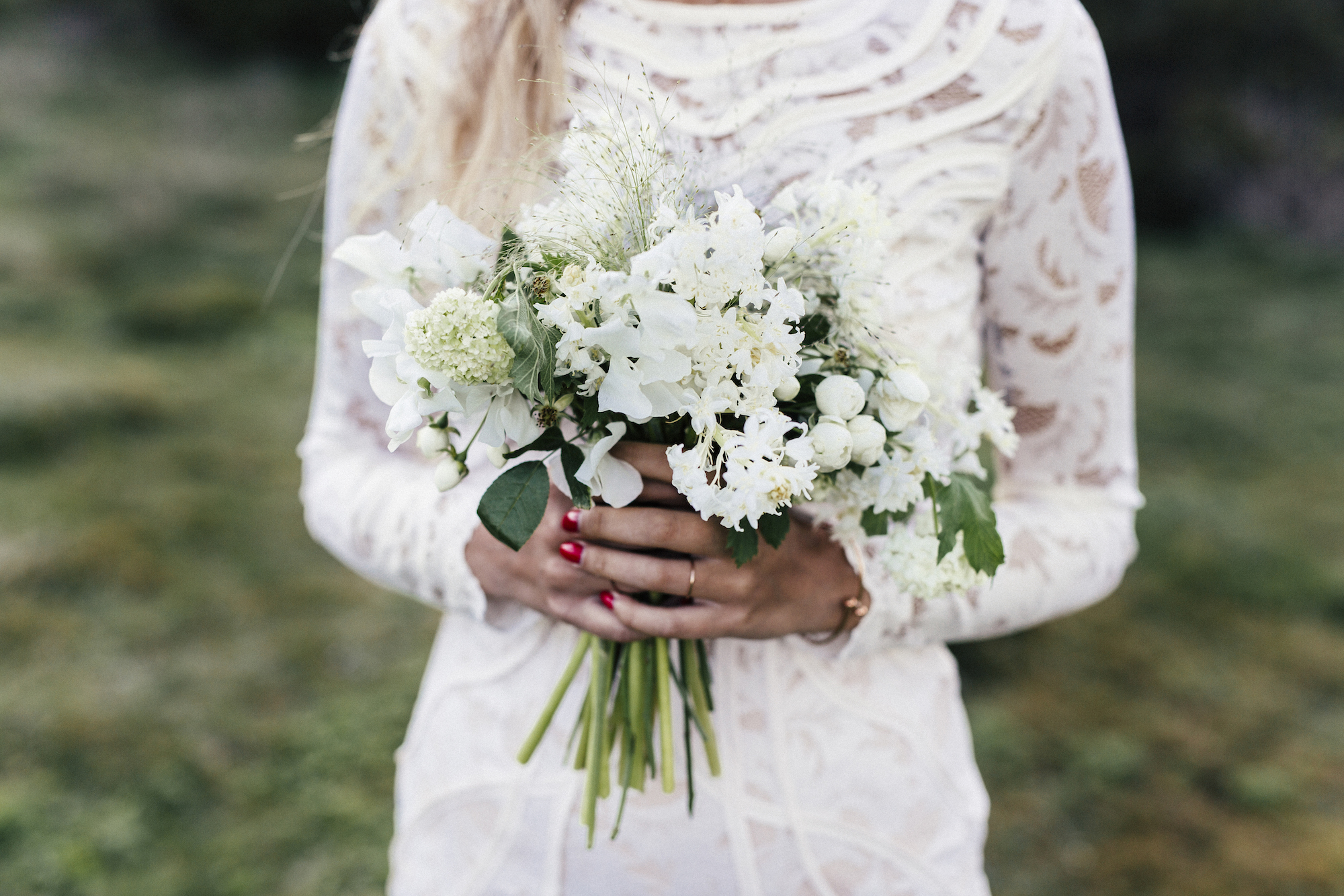 A bride wearing a lace long-sleeve wedding dress, holding flowers