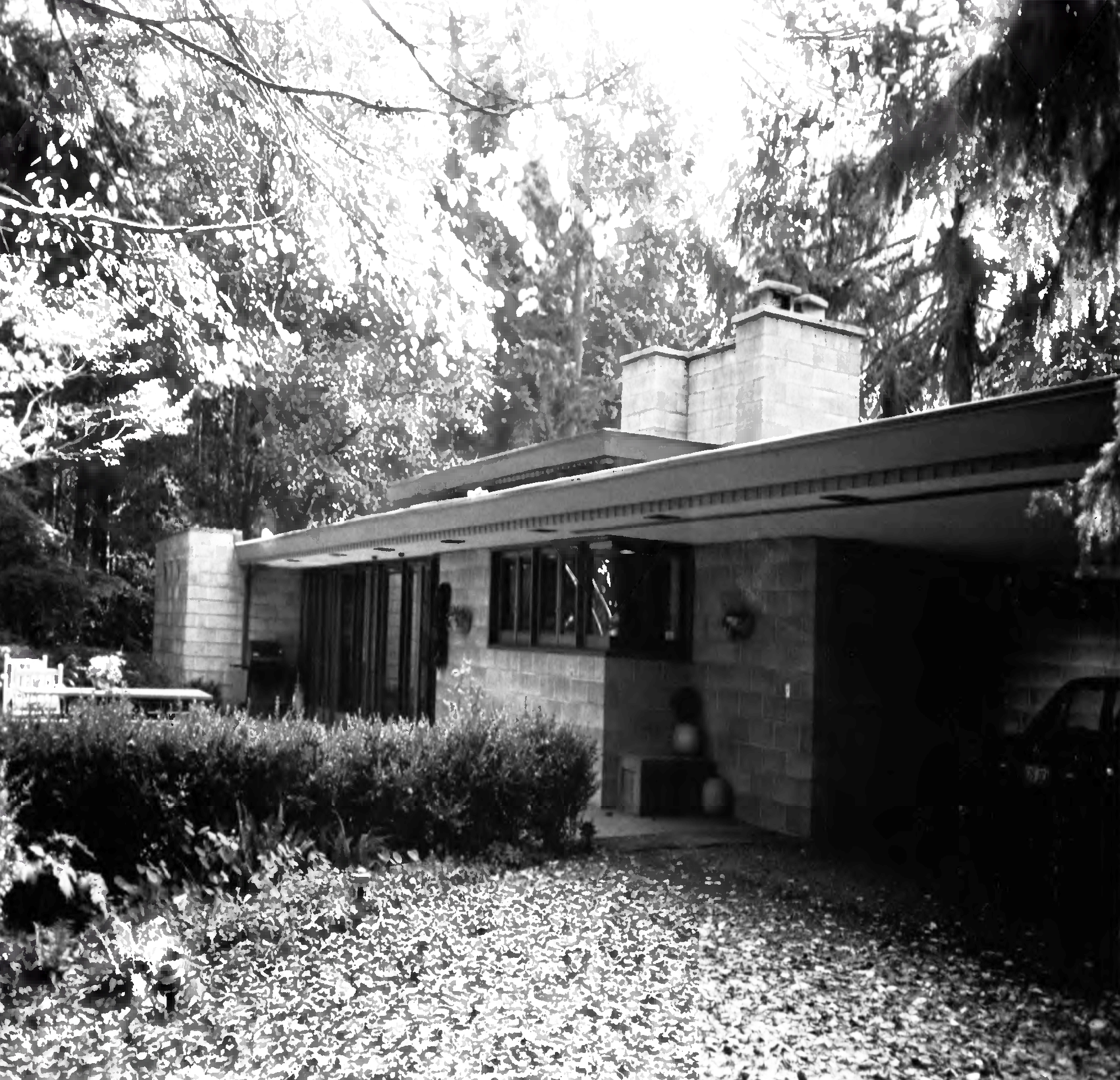 The Ray Z. Brandes house by Frank Lloyd Wright in Seattle. The house has a flat roof, brick facade, and a yard in front.
