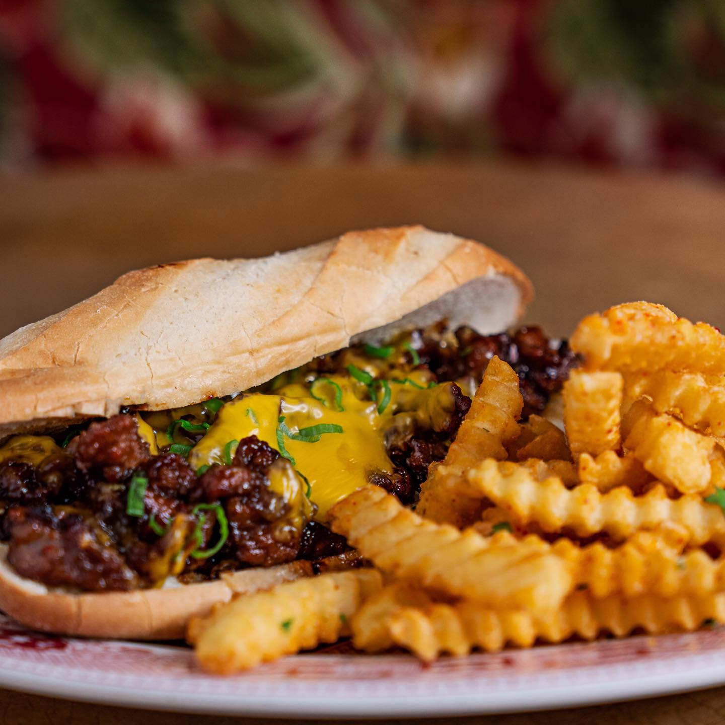 A cheesesteak on a long roll with crinkle cut fries