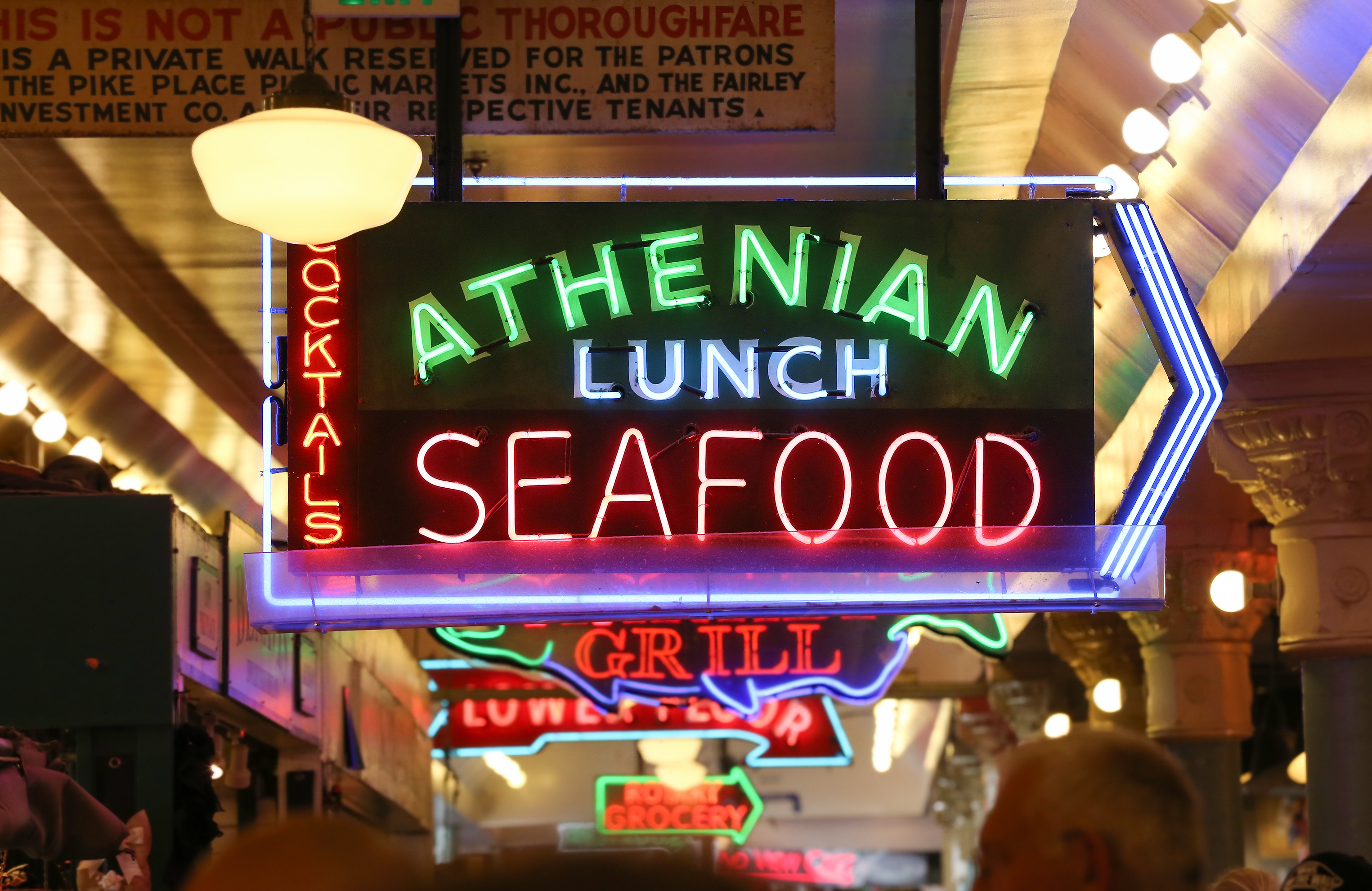 A neon sign that reads: Athenian Lunch Seafood Grill.