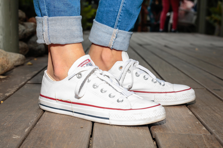A woman wearing Converse white sneakers