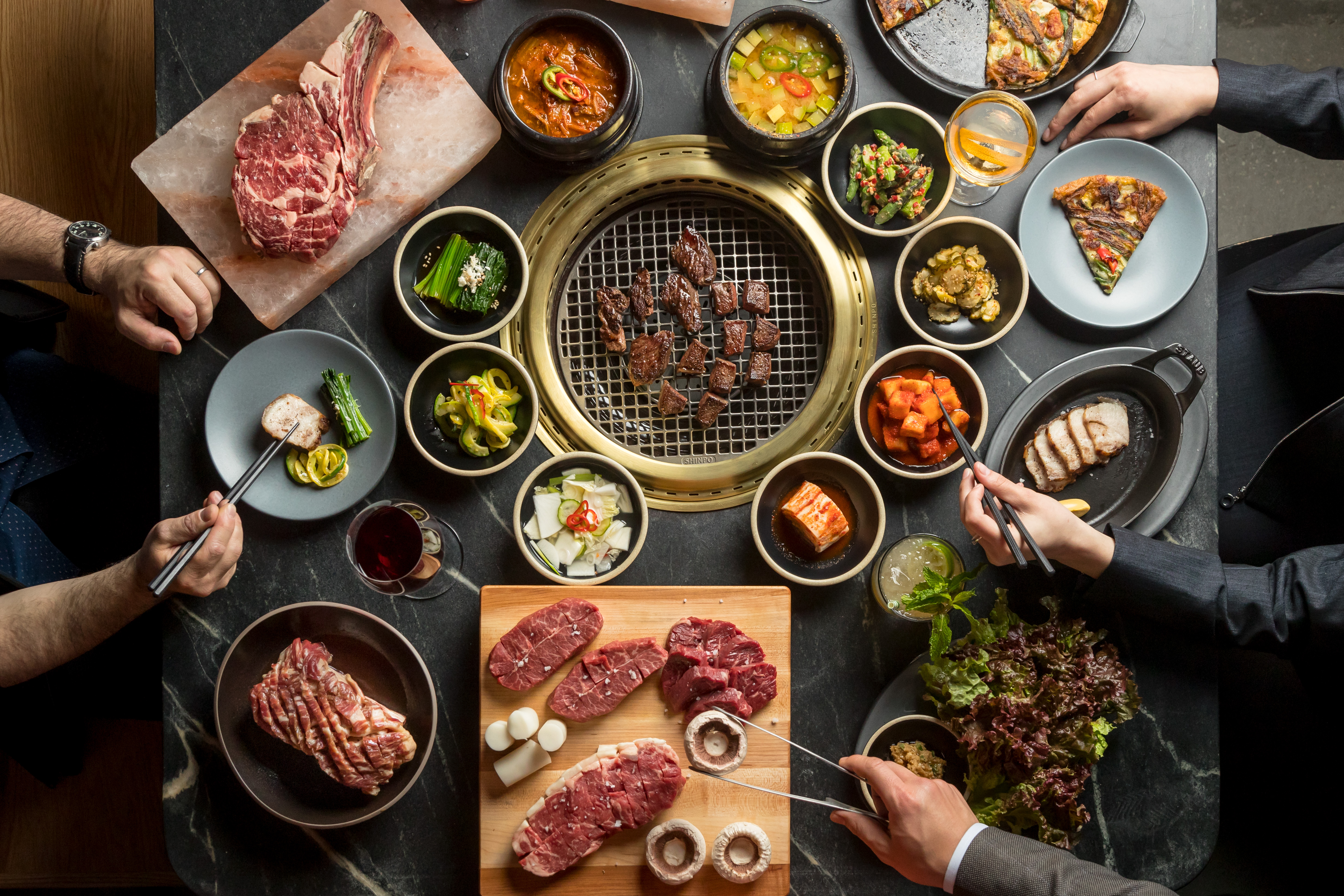 An overhead photograph of plates of banchan surrounding a Korean barbecue grill
