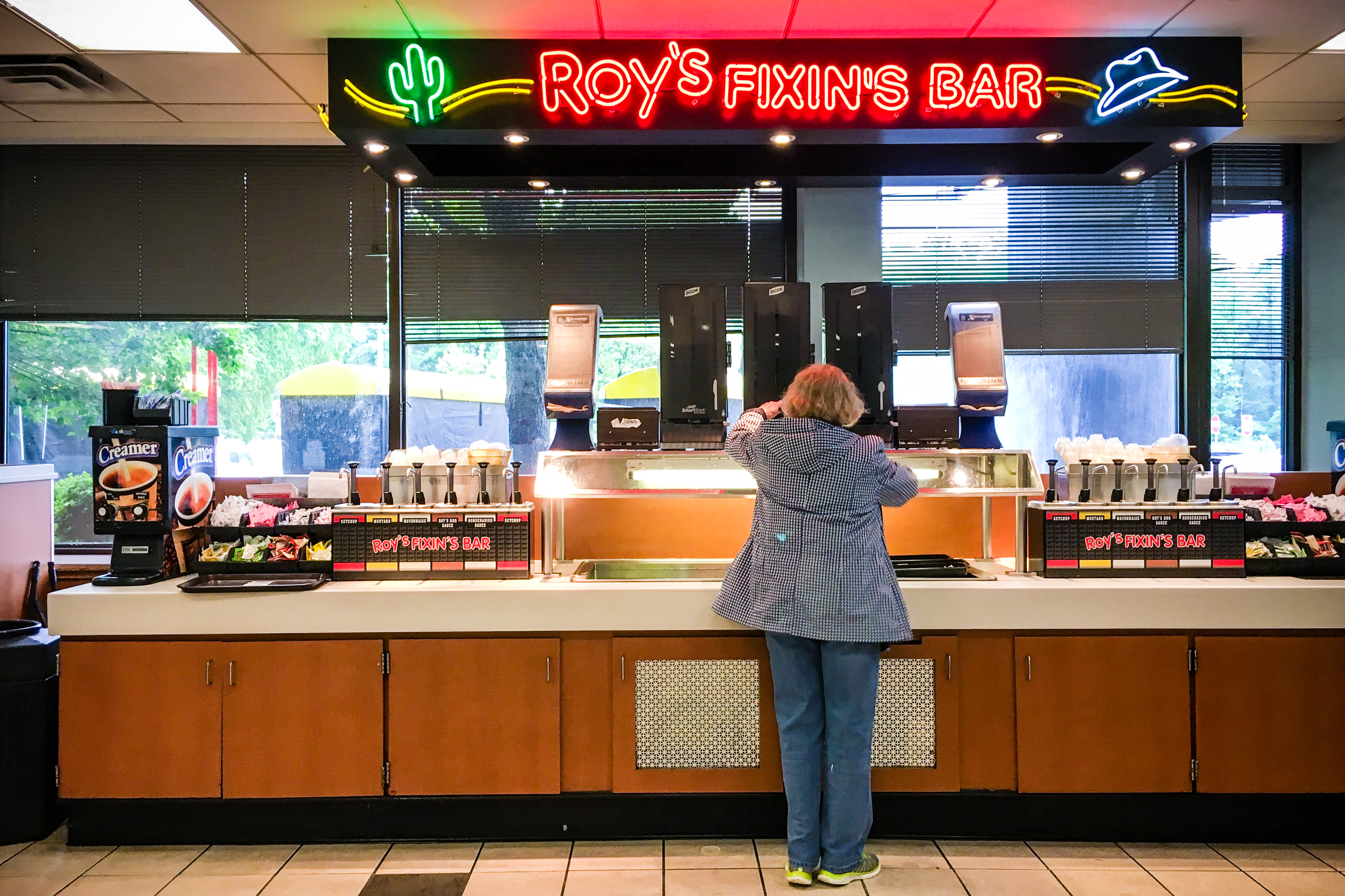 A woman serves herself at a Roy's Fixin's Bar at a rest area on the New Jersey Turnpike