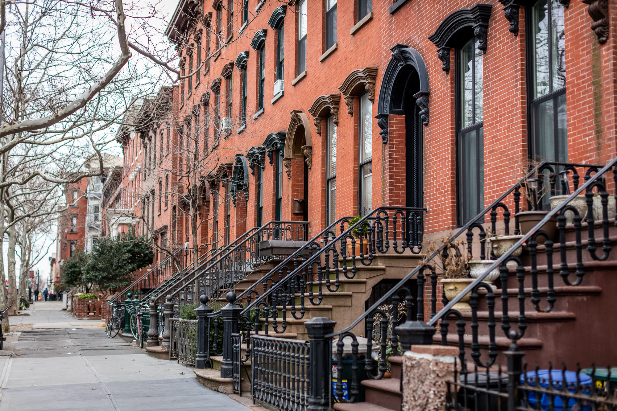 A row of red brick townhouses with wrought iron railings and stoops.