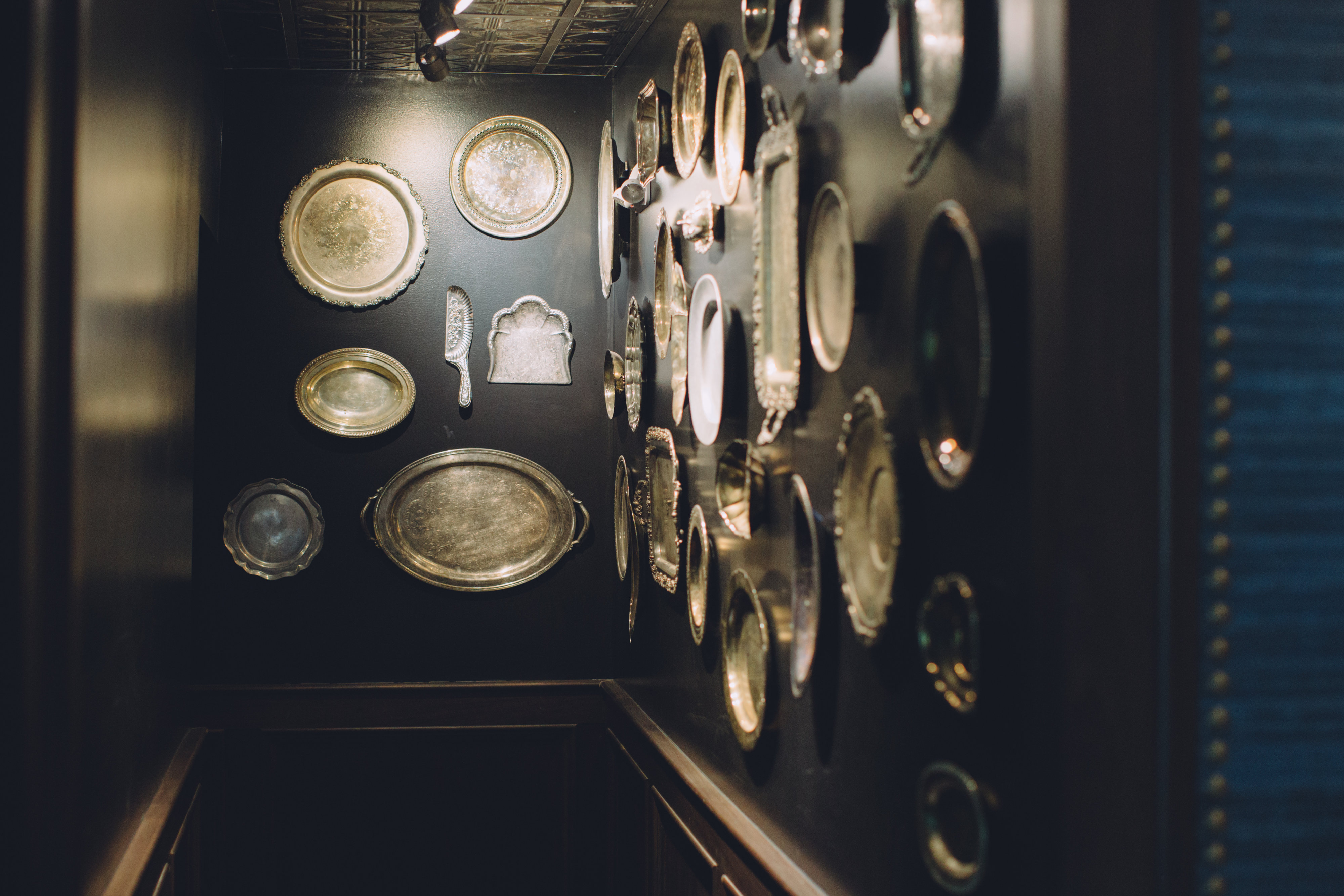 A collection of antique serving platters of various sizes hanging on the walls of Walloon Lake Inn.