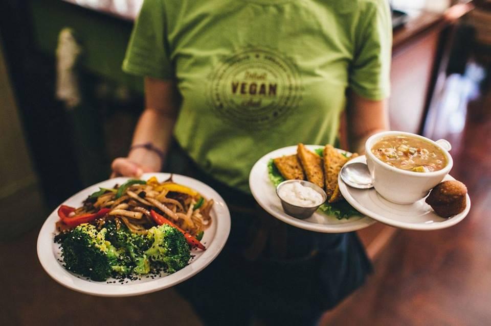 woman holding plates at detroit vegan soul