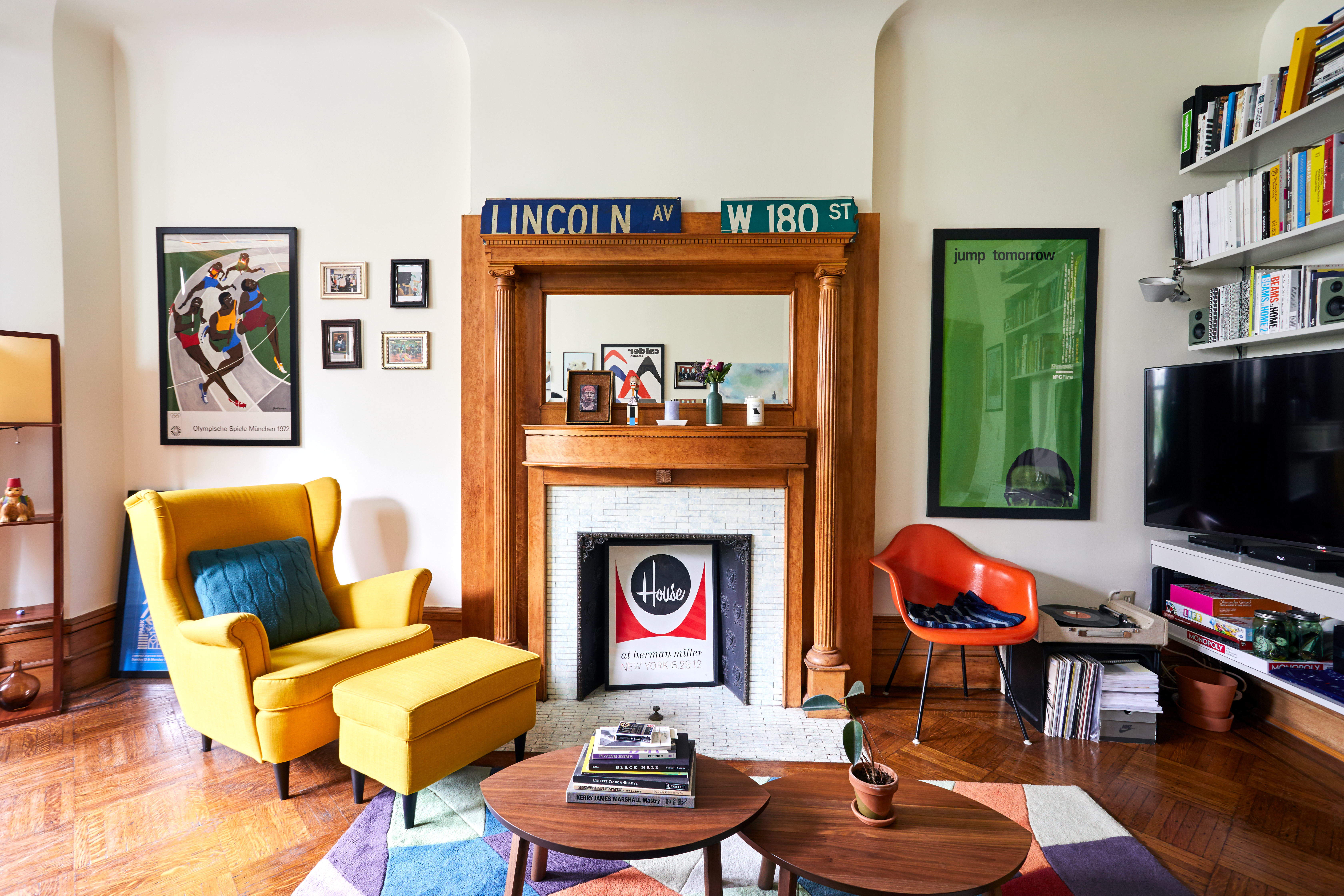The living area of a New York City apartment with a fireplace at the center, a yellow lounge chair with footrest to the left, and a red accent chair and television to the right. Bold bright artworks hang around the walls.