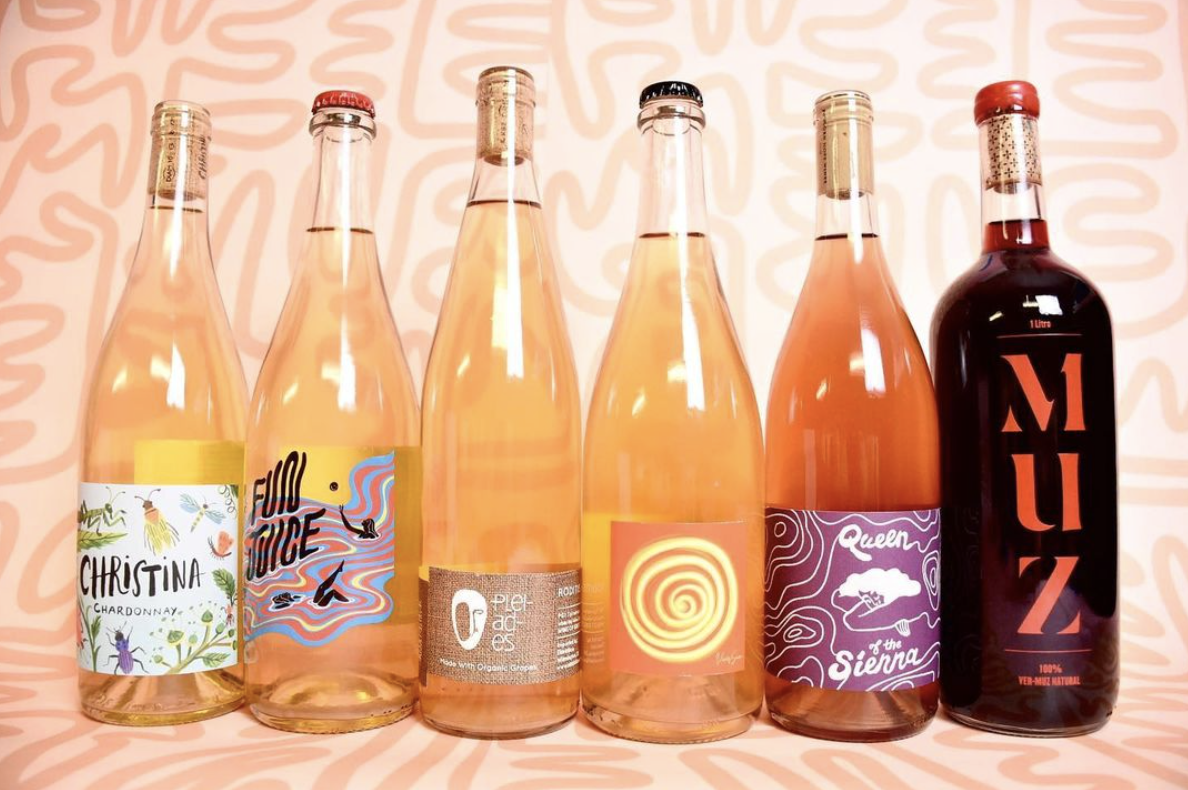 A selection of light-colored natural wine bottles from La Dive against a bright orange background with squiggly lines