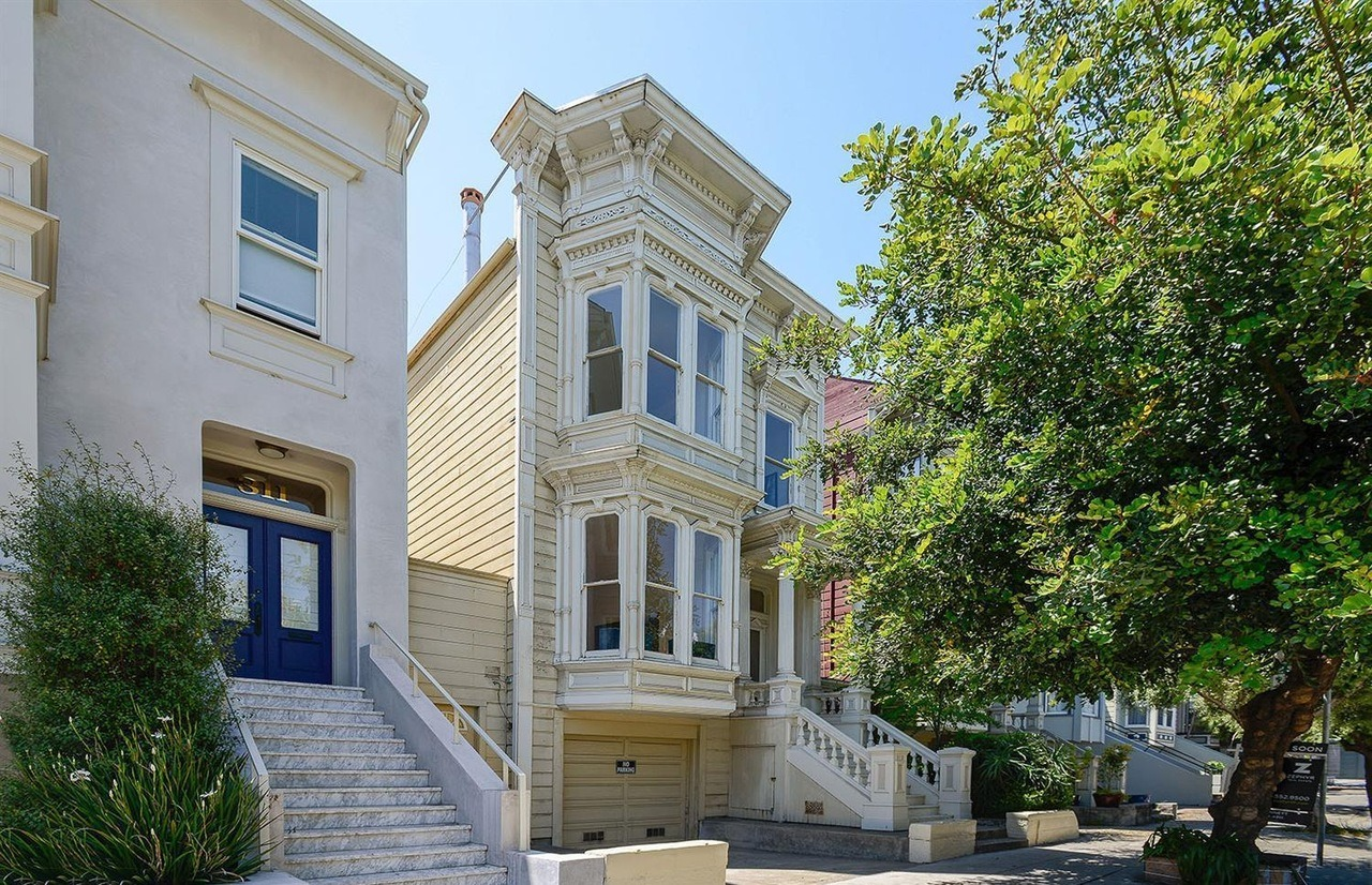 A tall, white, Italianate Victorian house on Haight street with Corinthian columns on the porch.