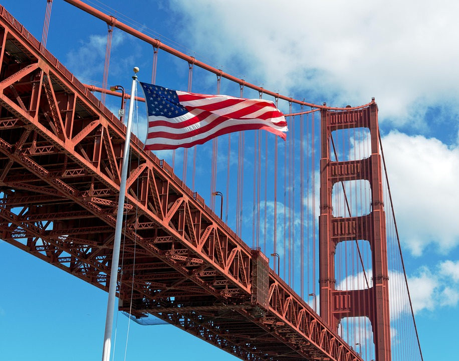 An American flag flapping near the northbound lanes of the Golden Gate Bridge.