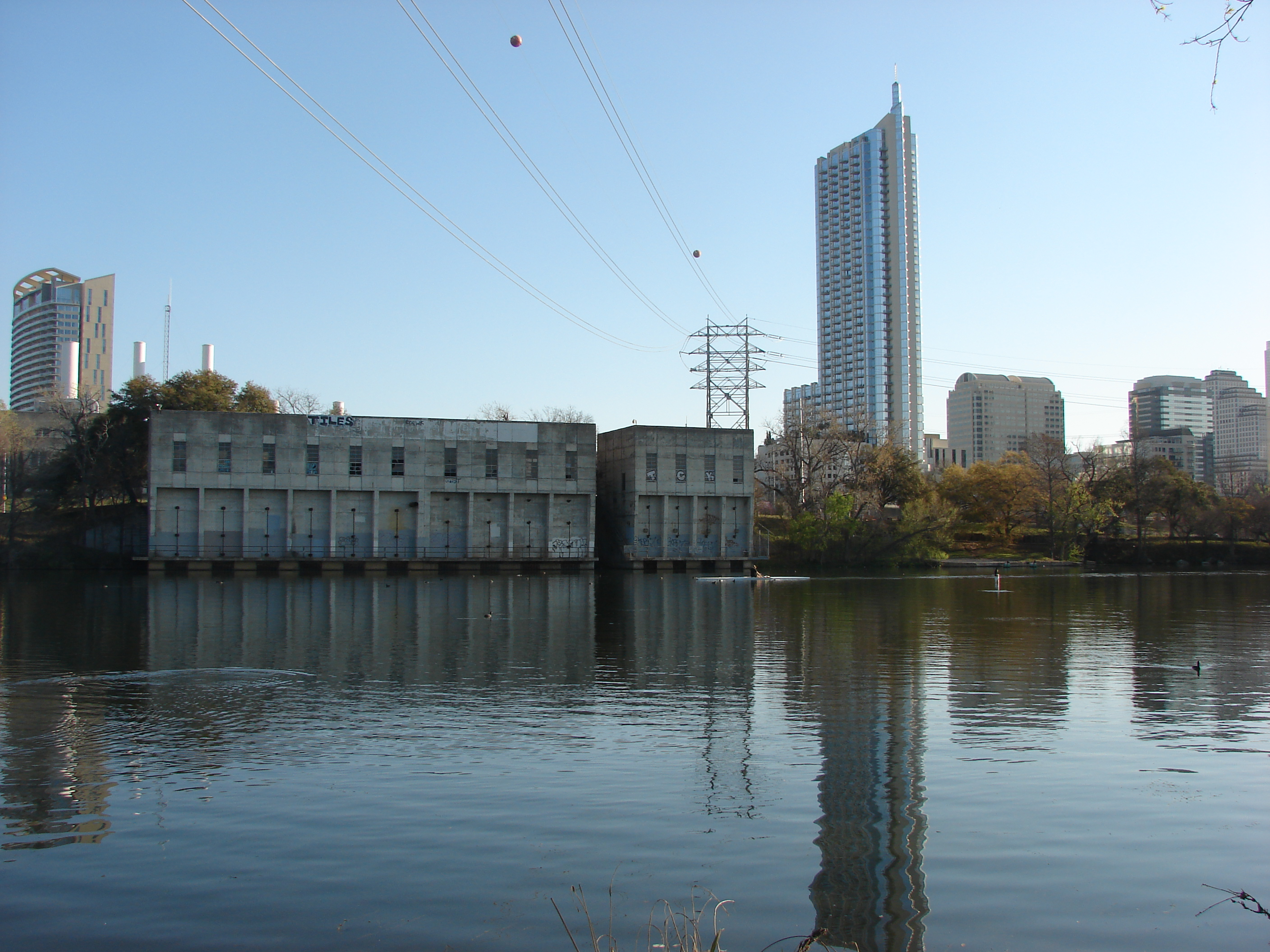 Former power plant intake on lake with a couple of skyscrapers behind