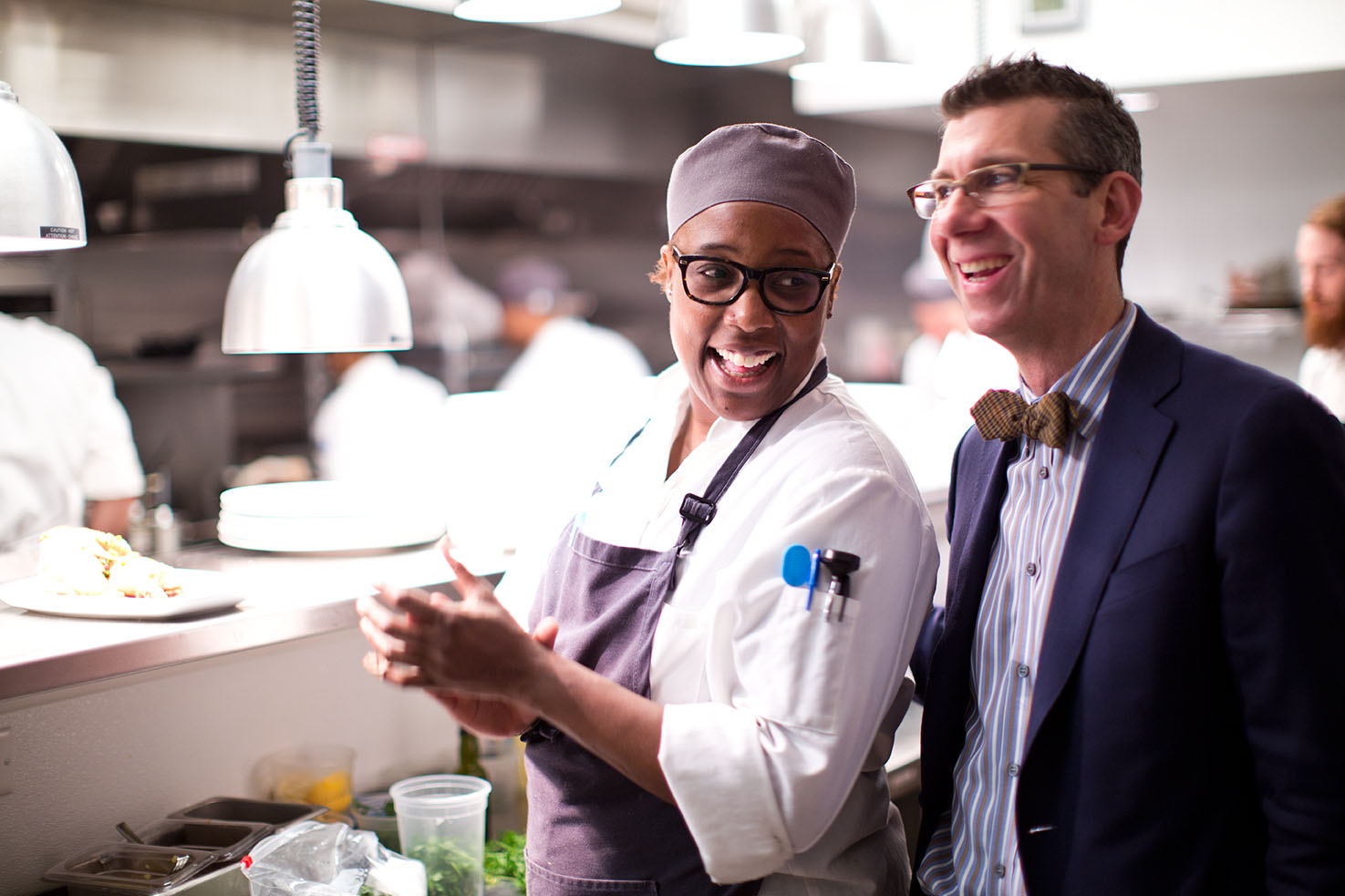 A woman and a man in a restaurant kitchen