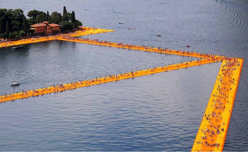 An aerial photo of hundreds of people walking along a network of piers floating in the water. The piers are painted bright orange and gold.