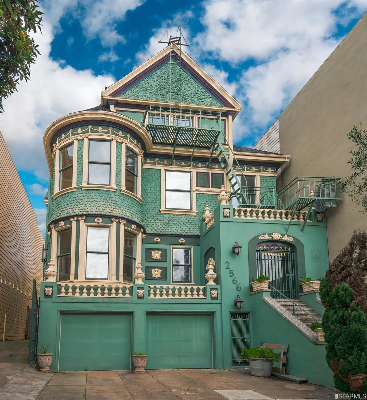 A green Queen Anne Victorian house.