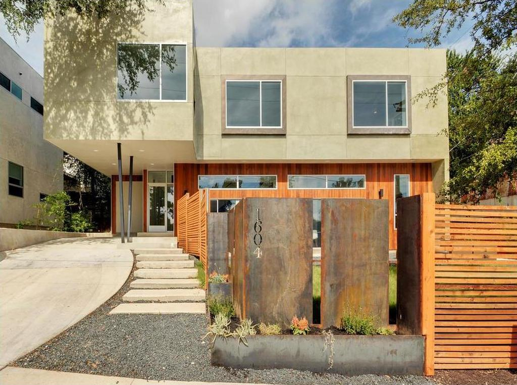 Two-story stucco-and-wood contemporary with wood and Cor-ten metal front fence