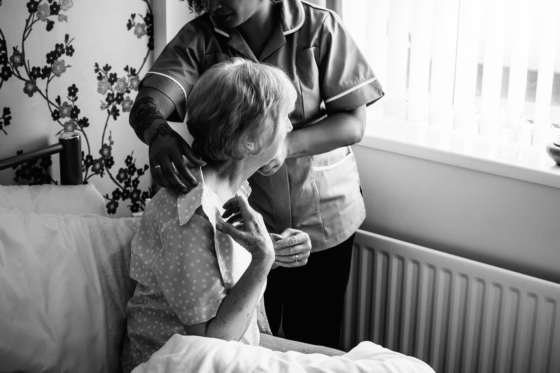 A home caregiver helps a senior woman get dressed in her bedroom.