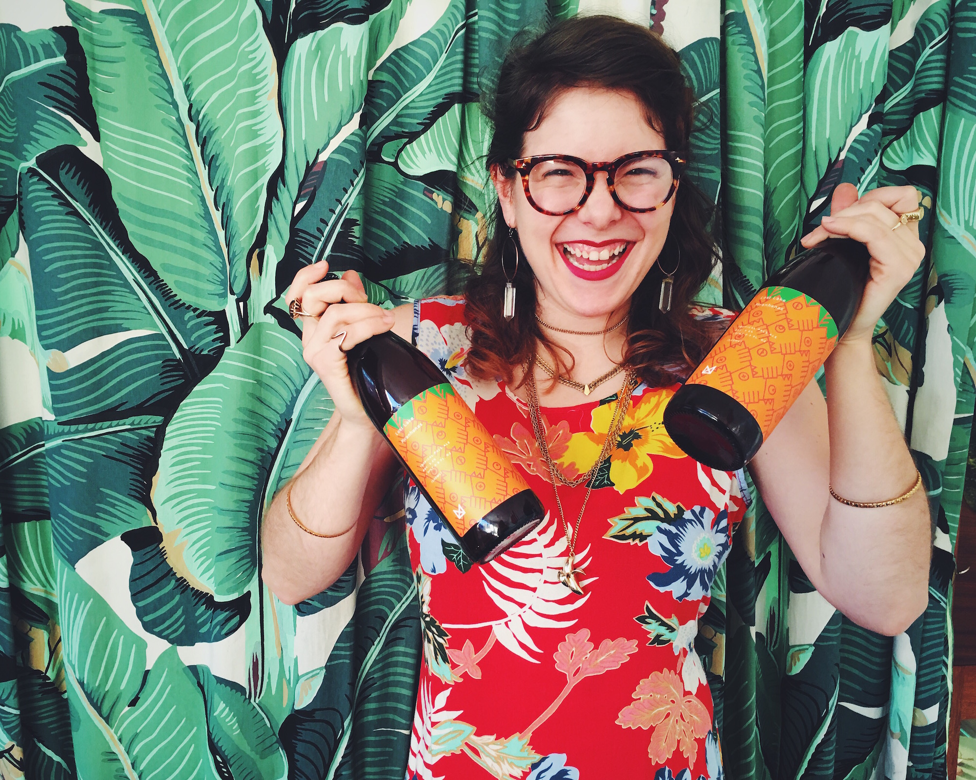A woman in tropical clothing holding bottles of alcohol