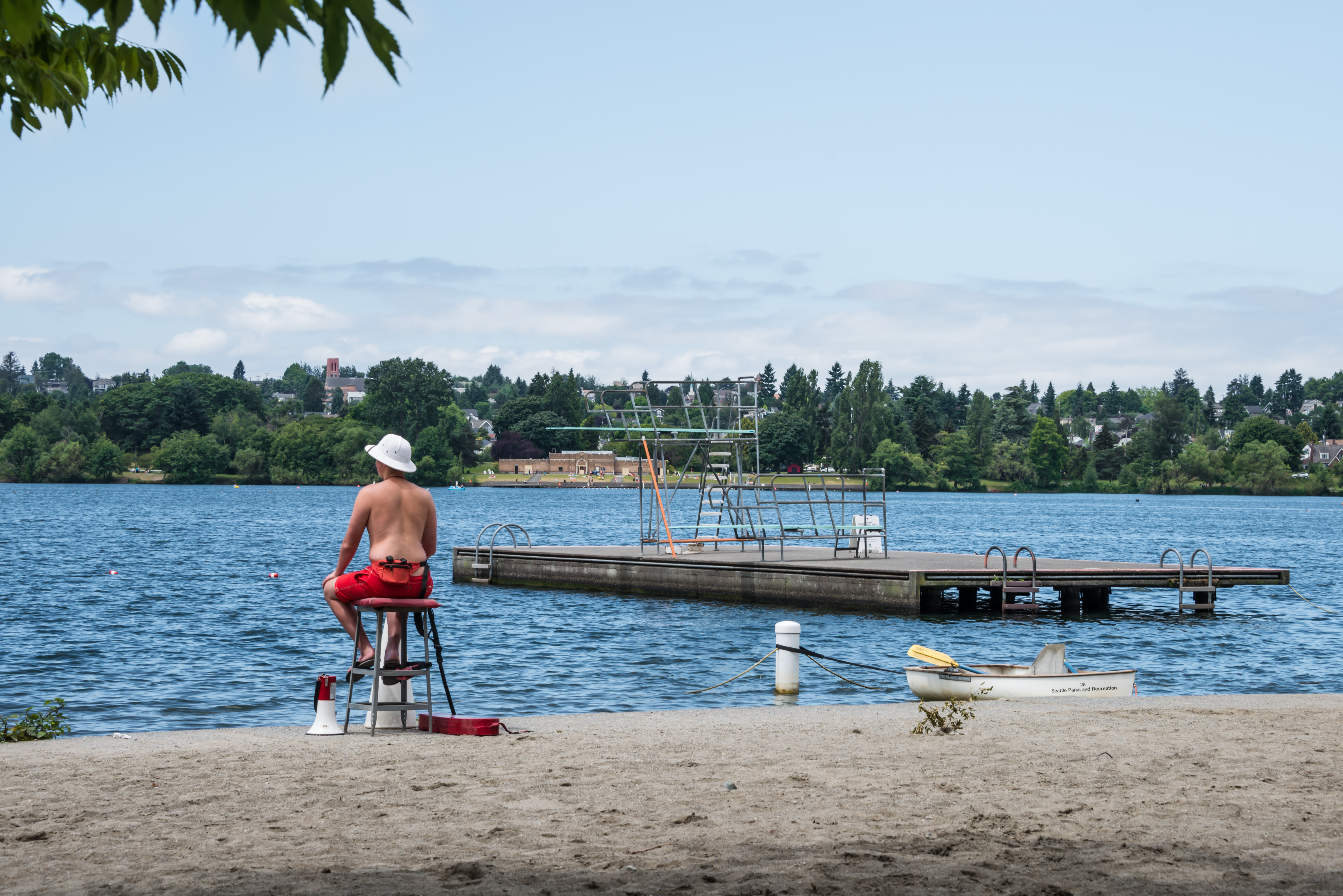 In the foreground is a sandy beach. A lifeguard is sitting on a tall chair on the beach. In the distance is a wooden pier in a body of water.