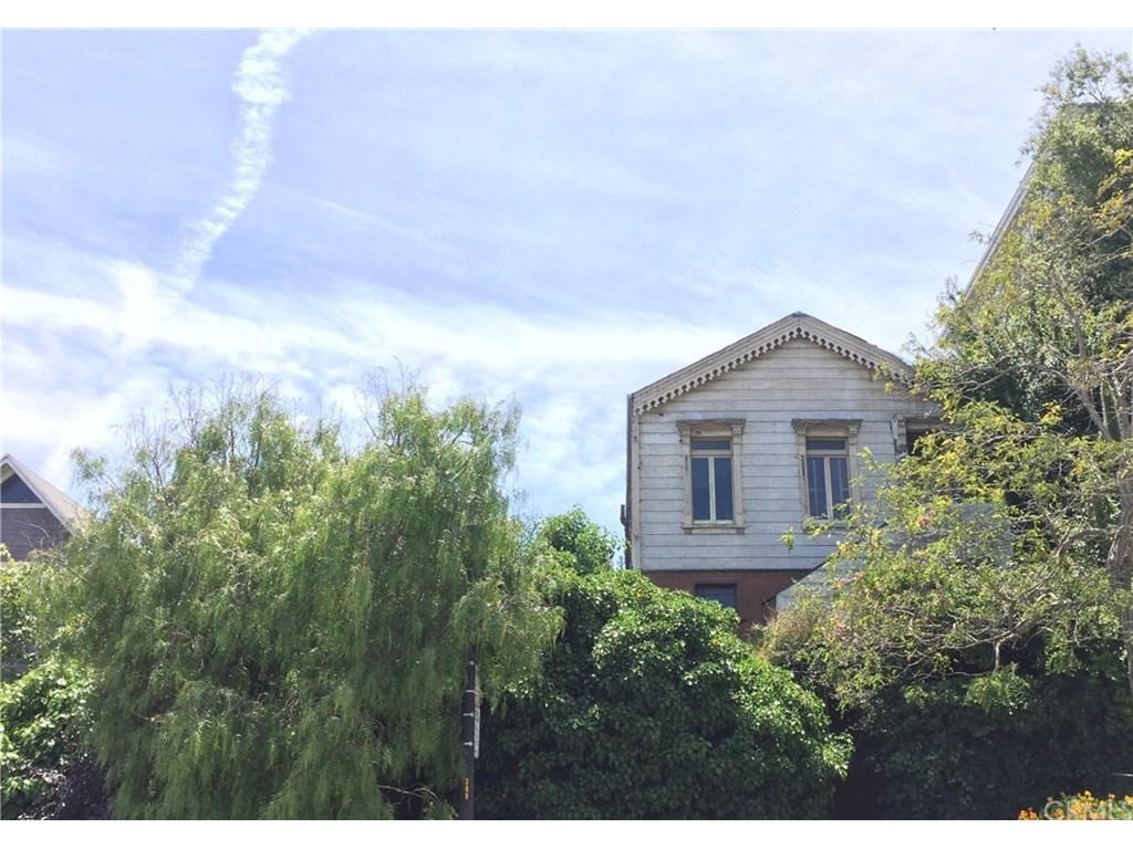 Edwardian teardown home in overgrown shurbbery.