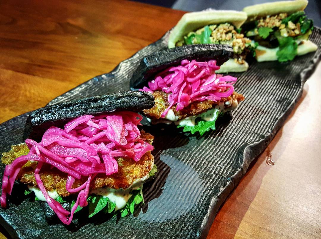 Four bao are on a long, narrow tray. The two in the forefront are black and made of squid ink. Bright pink pickled onions are visible inside.