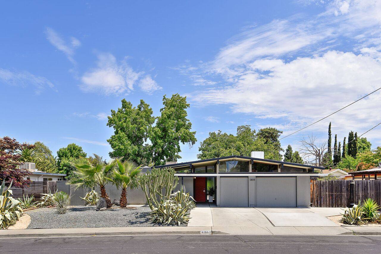A white mid-century home with a red front door.