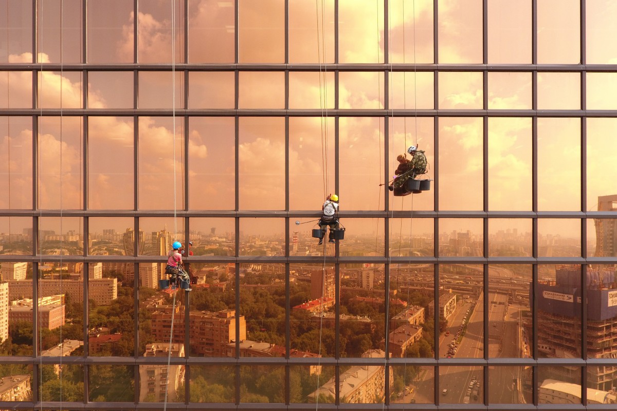 Shot of three men suspended from the side of a reflective, copper-colored side of a skyscraper with the cityscape reflected in the glass.