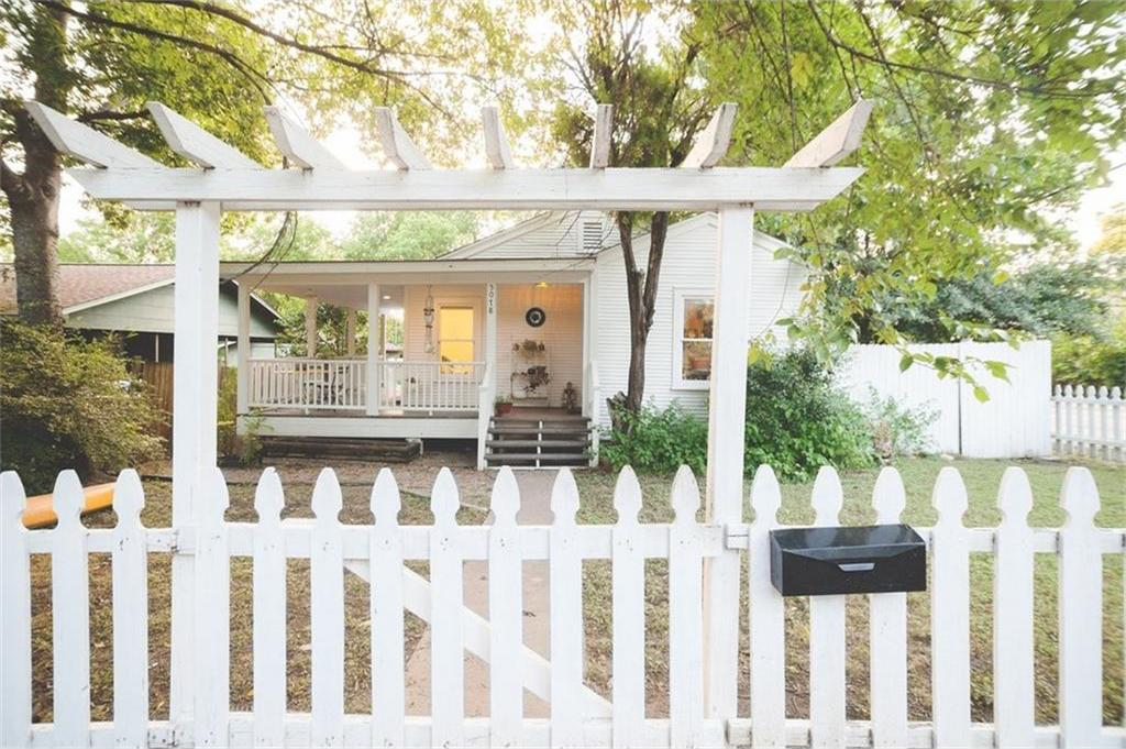 White frame vintage home seen through front fence/entrance