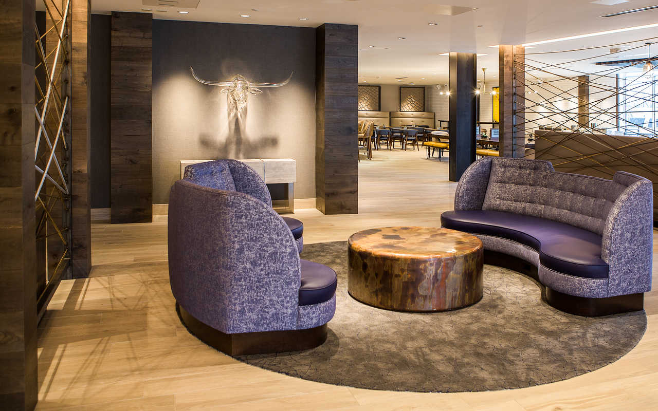 Hotel lobby with purple couches and a glass sculpture of a steer