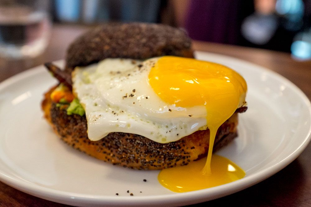 A breakfast sandwich on a poppy seed roll with an oozing fried egg on top