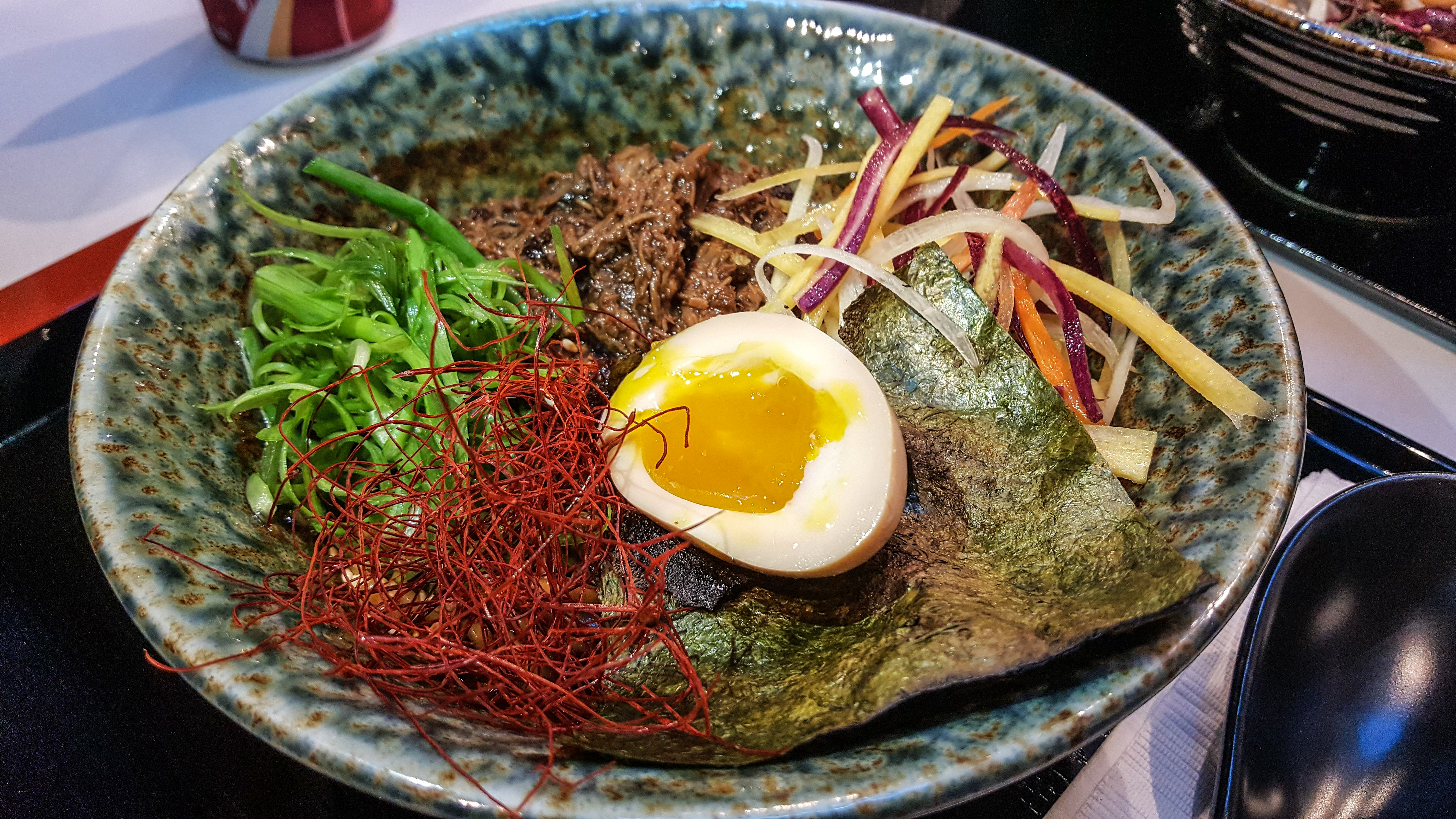 A bowl of ramen with saffron, a soft egg, seaweed, and chopped vegetables