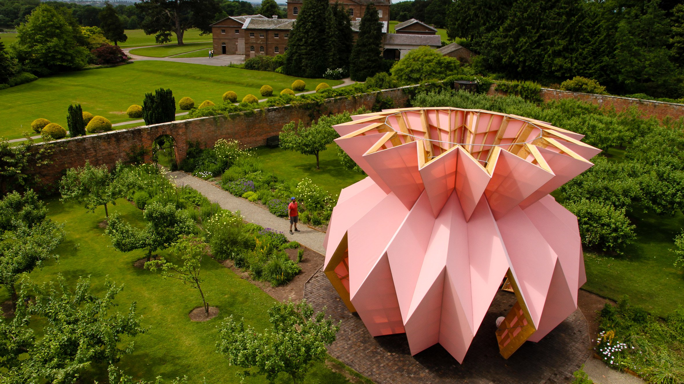 An open temporary structure with a wooden frame and faceted like a pineapple sits within a walled garden.