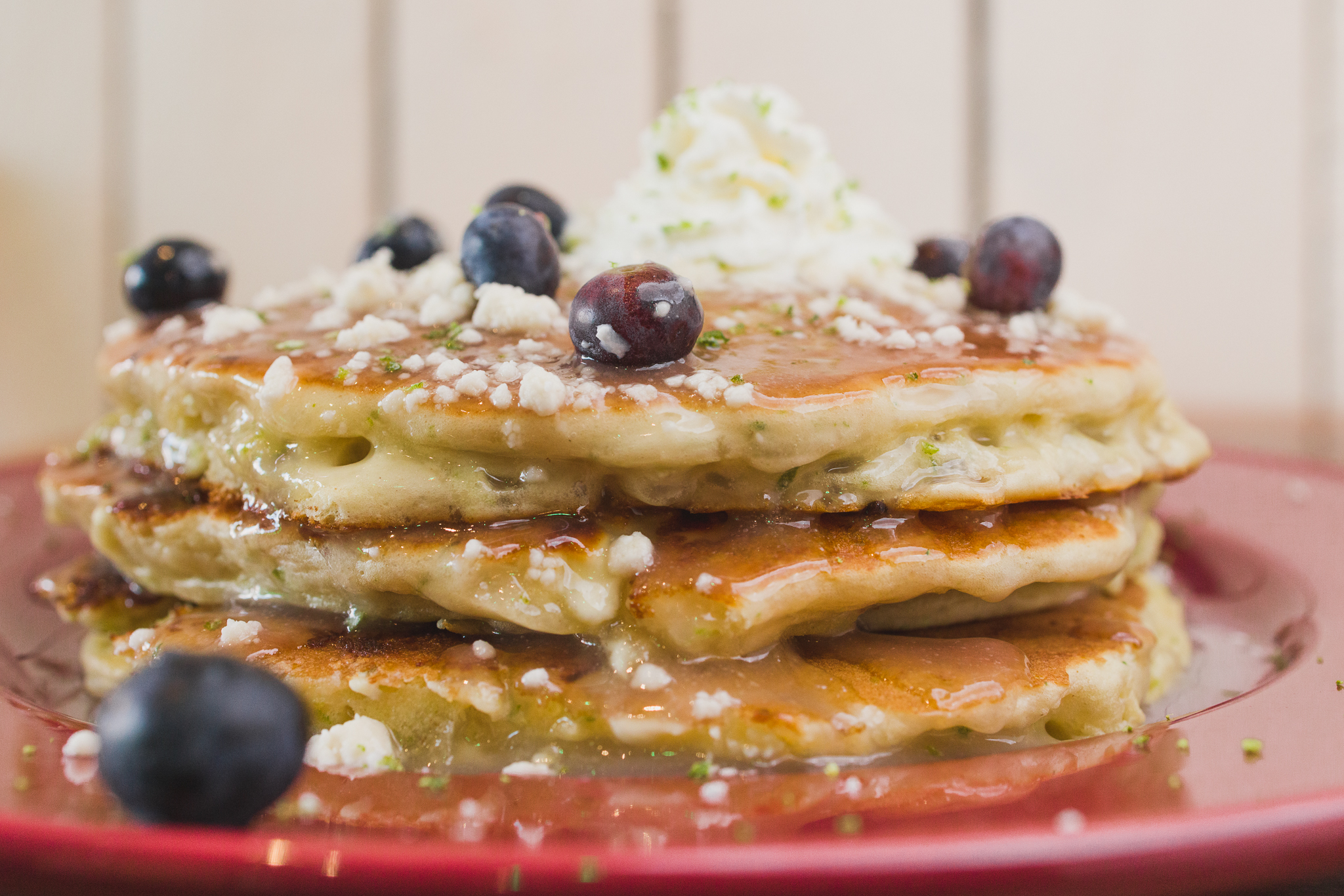 A stack of pancakes with syrup, blueberries
