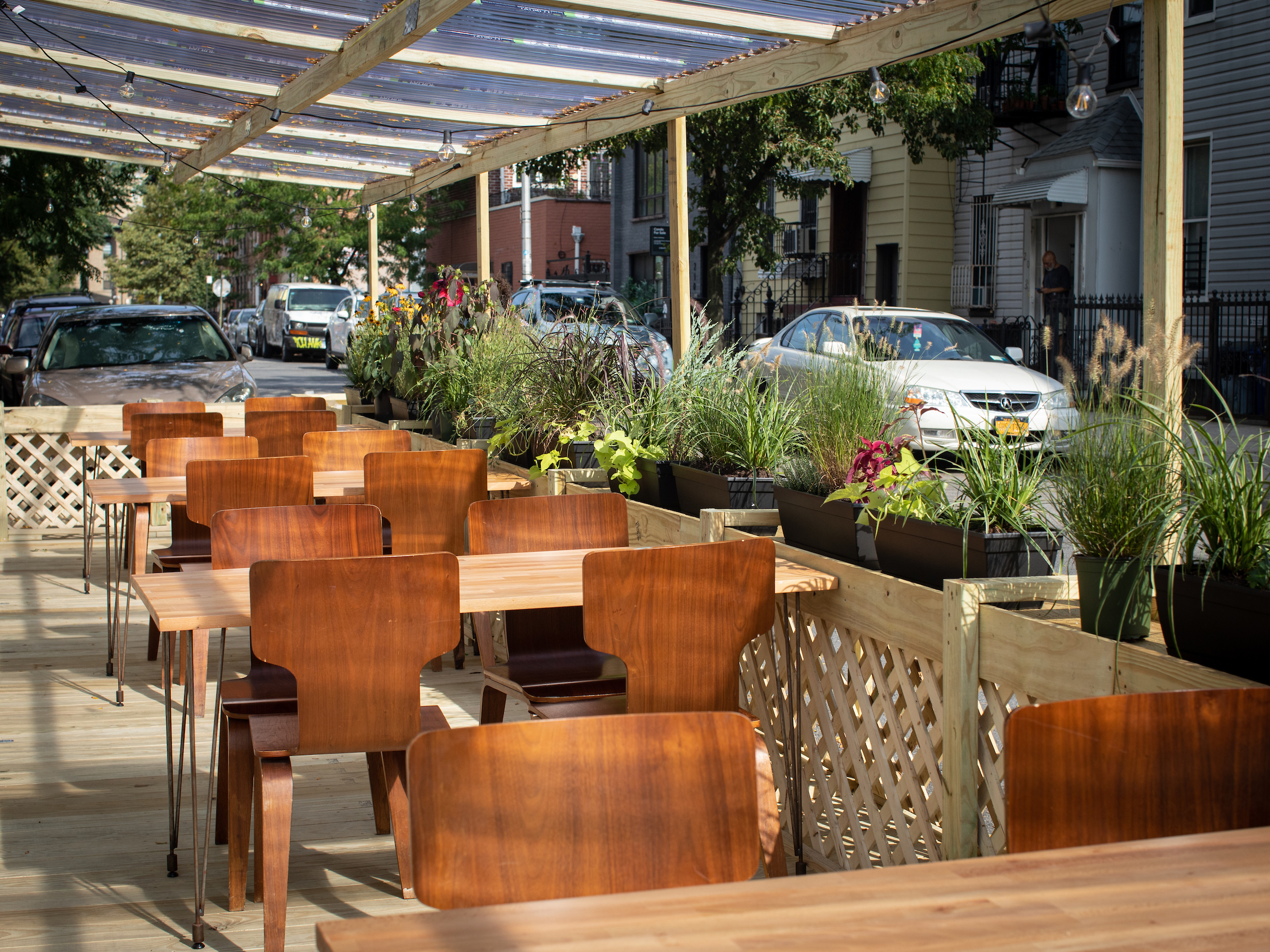 A restaurant's outdoor seating area, with a few tables, wooden chairs, and cars visible in the background