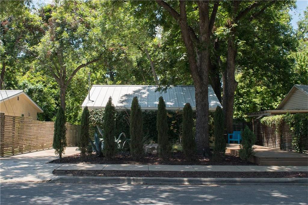 Small house behind row of midsized Italian cypress trees