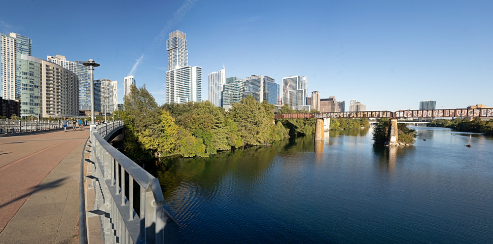 Photo of a city downtown. A curved pedestrian trail is in the foreground on the left. A river crossed by a rusty trestle railroad bridge curves in the same direction. A group of very tall buildings is farther back in the center. There is a group of dormant and semi-dormant trees along the river.