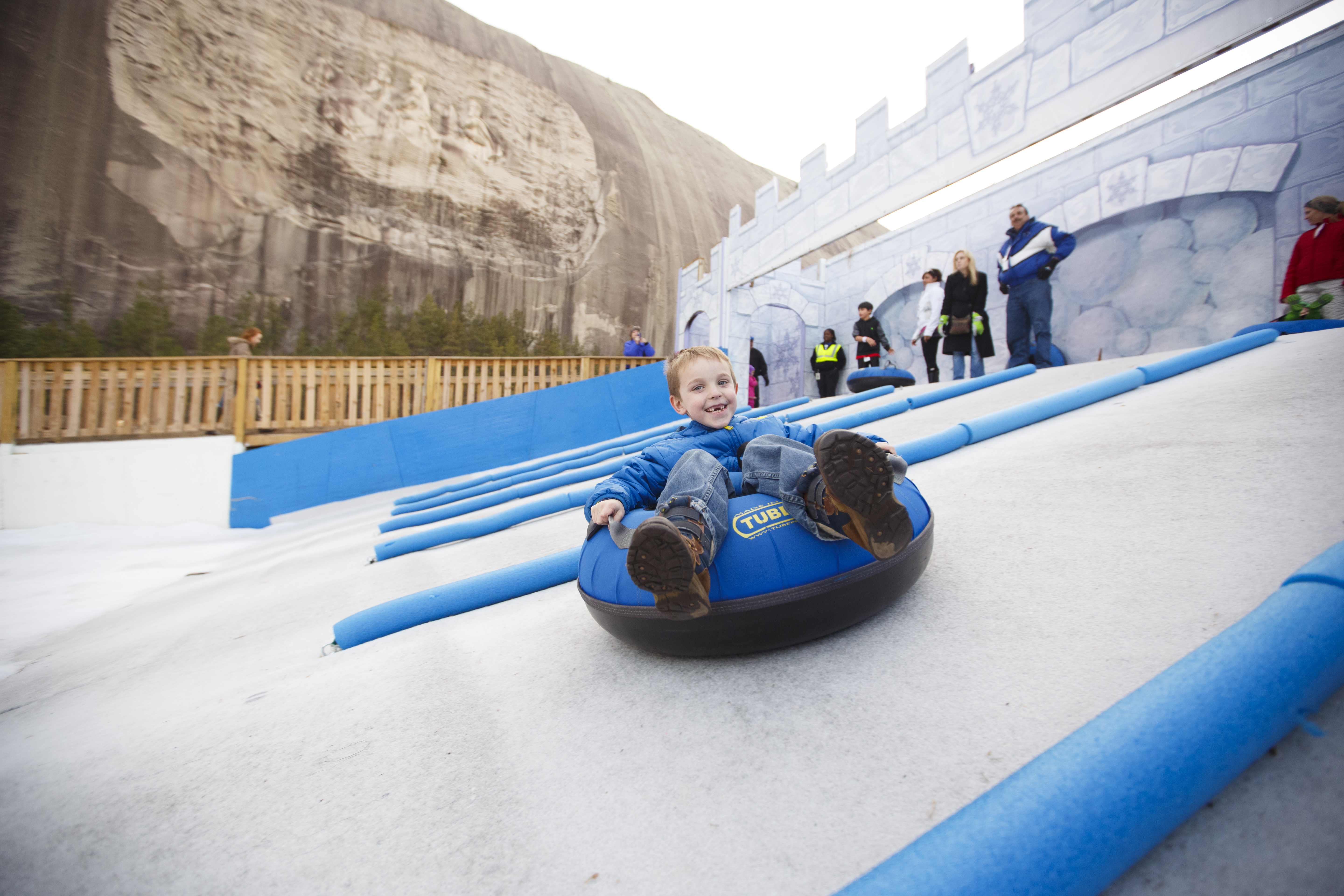 Child snow tubing with Stone Mountain in the background.