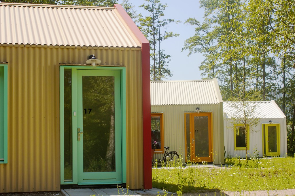 Side view of three small homes with corrugated walls and colorful door and window frames.