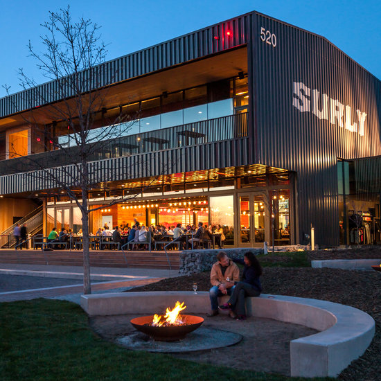 An exterior late summer shot of Surly's monolith brewery. The bottom floor is filled with people inside. One couple is outside, near a fire pit by its giant outdoor green space.