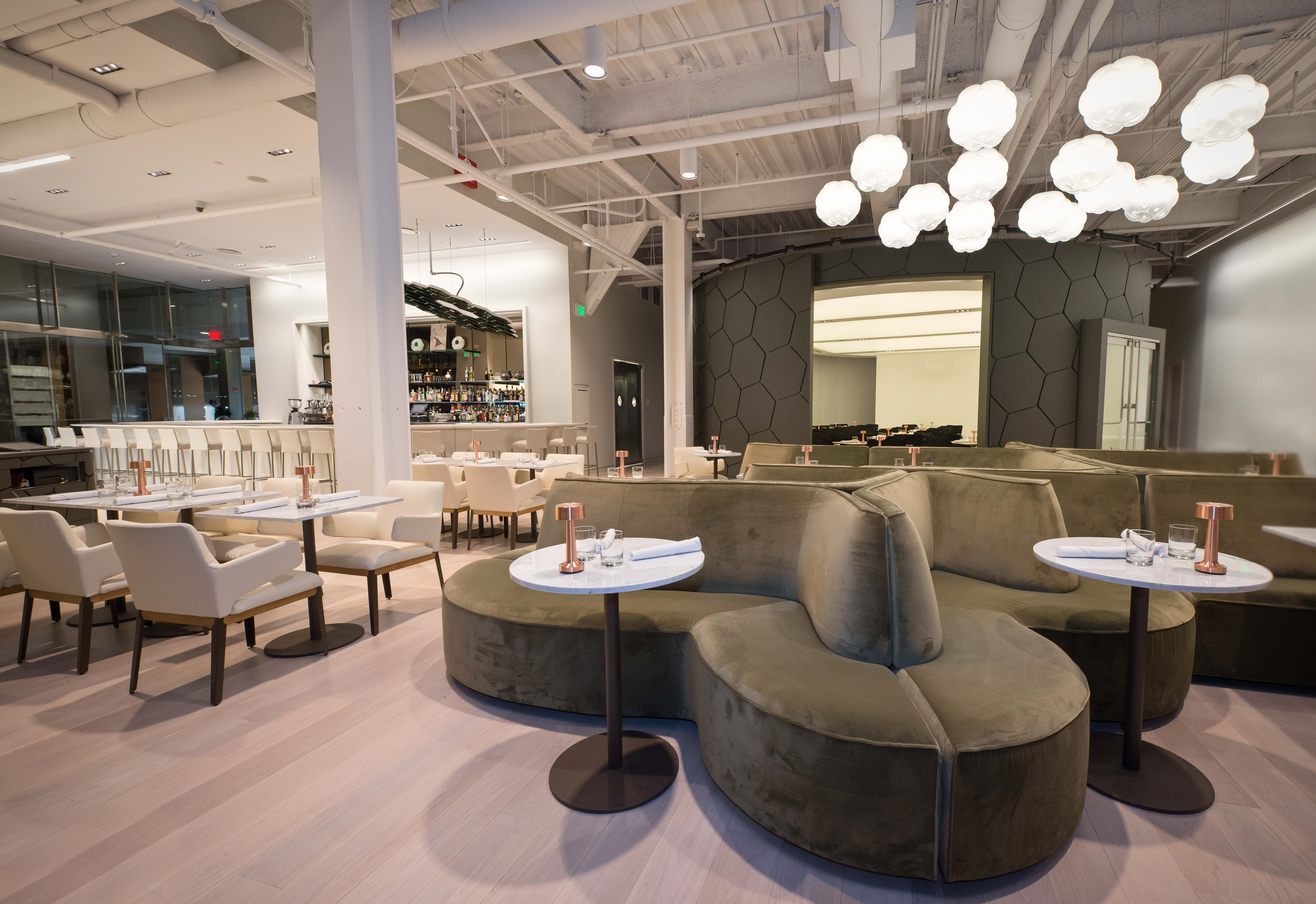 The interior of a restaurant with geometric white light fixtures, curved olive green booths, and mostly white accents