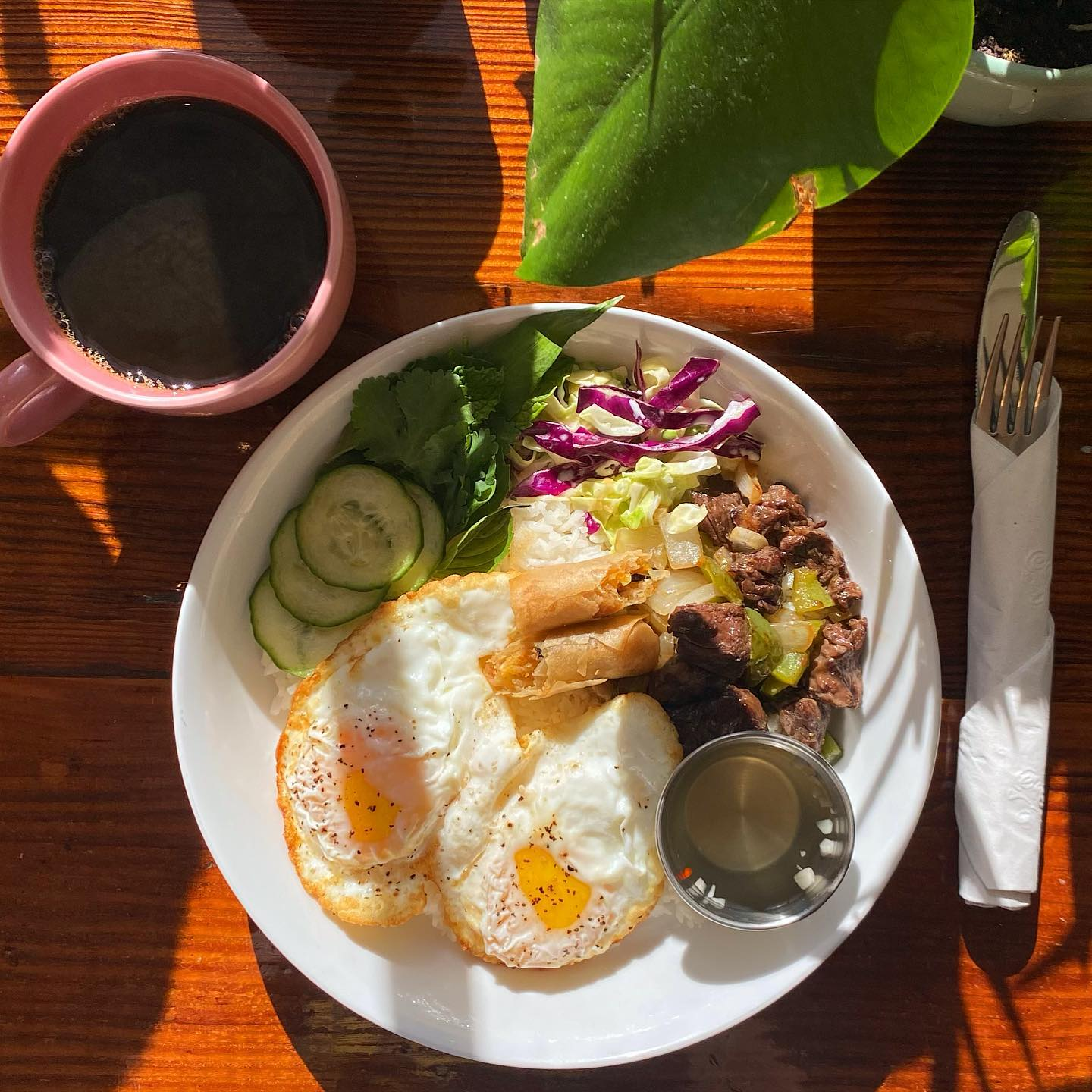 two eggs, cucumber, coffee, and steak on a white plate