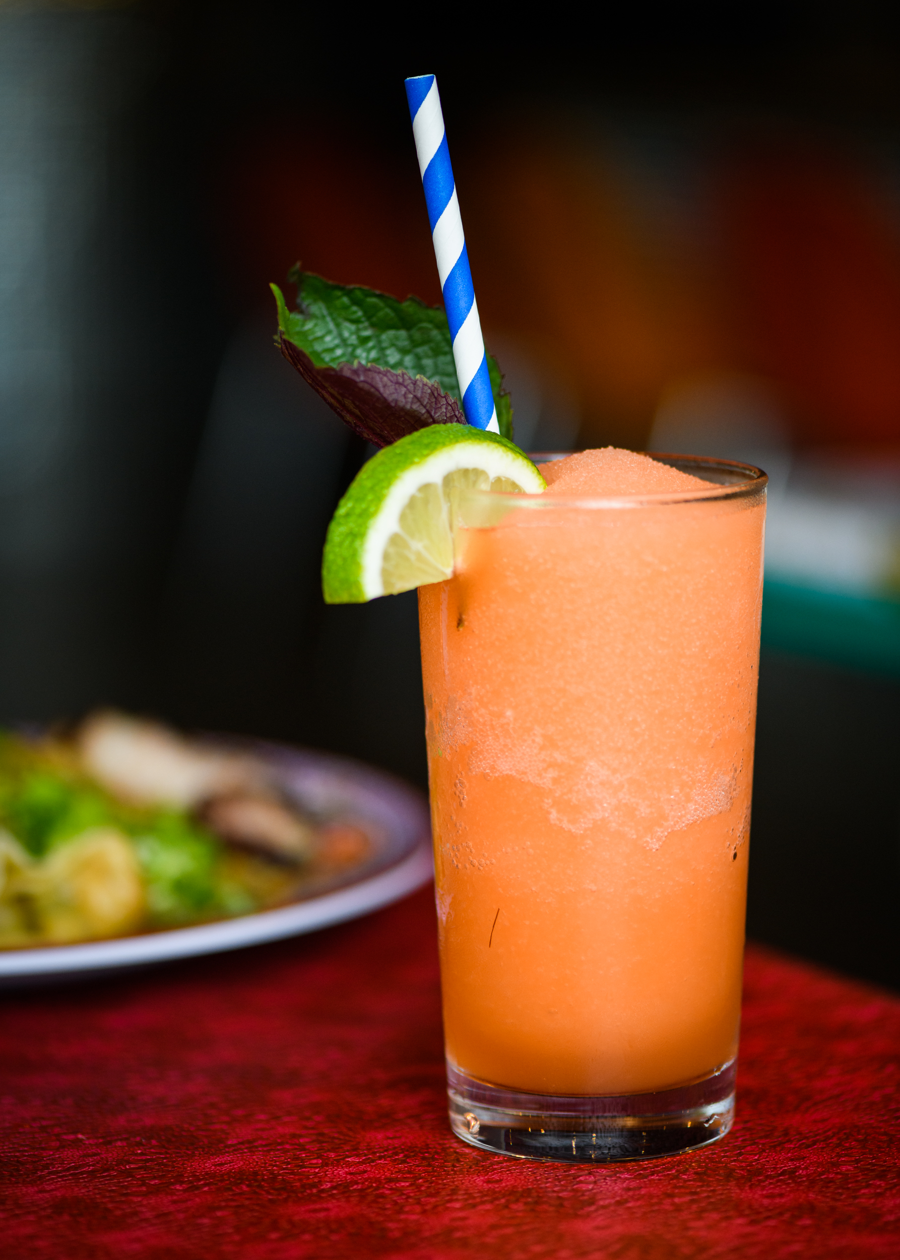 An orange slushie is poured into a tall glass with a lime and a blue-and-white straw. A Malaysian char siu dish is out of focus behind it.