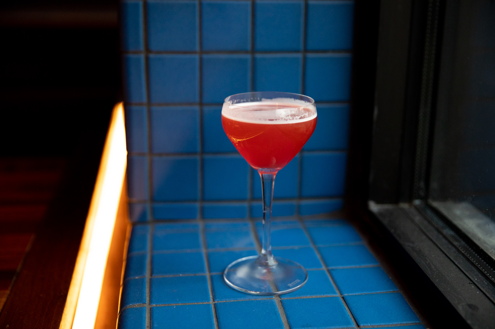 The bright red cocktail is in a coup glass on a window sill covered in blue tile.