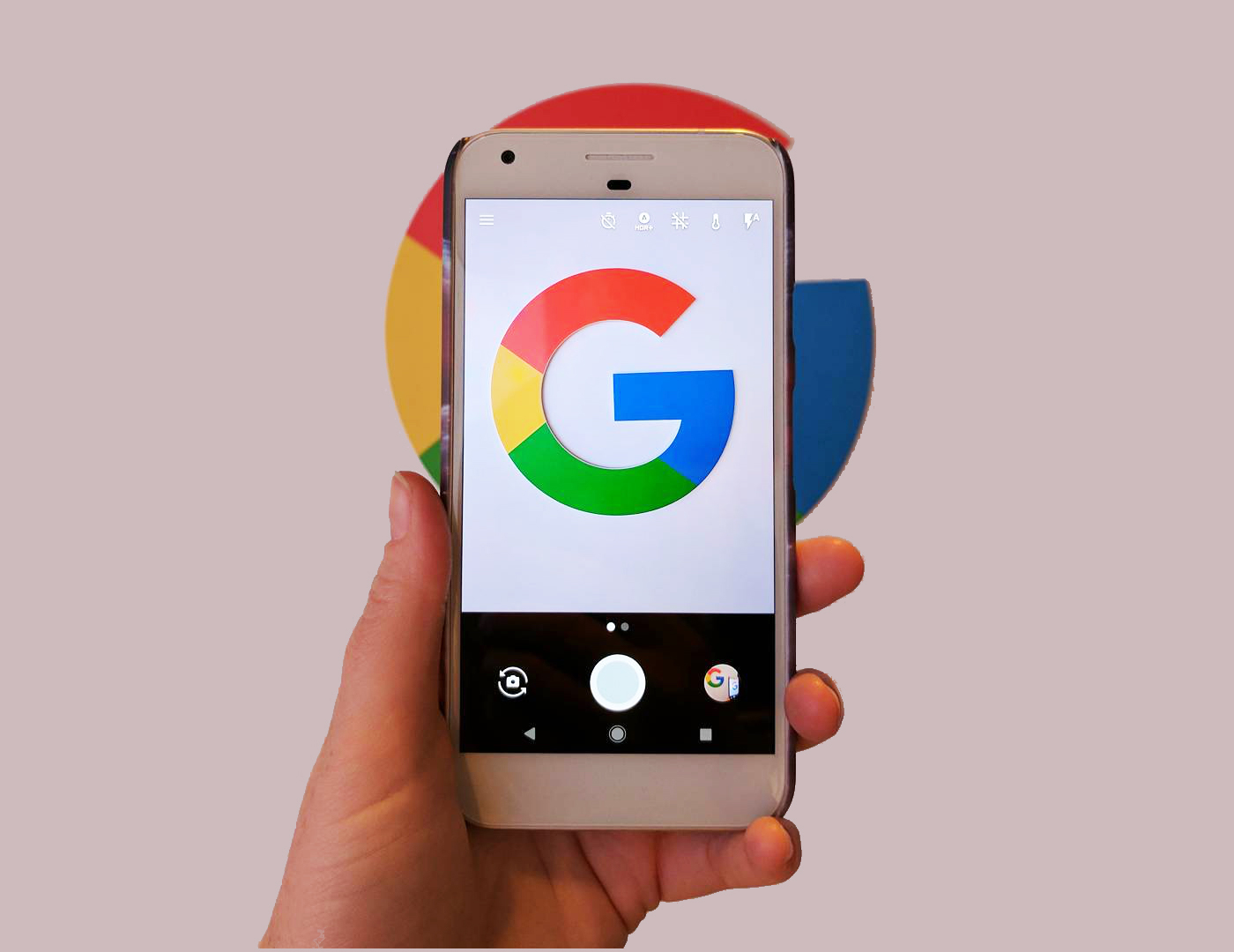 The Google pixel phone held by a hand on a pinkish background