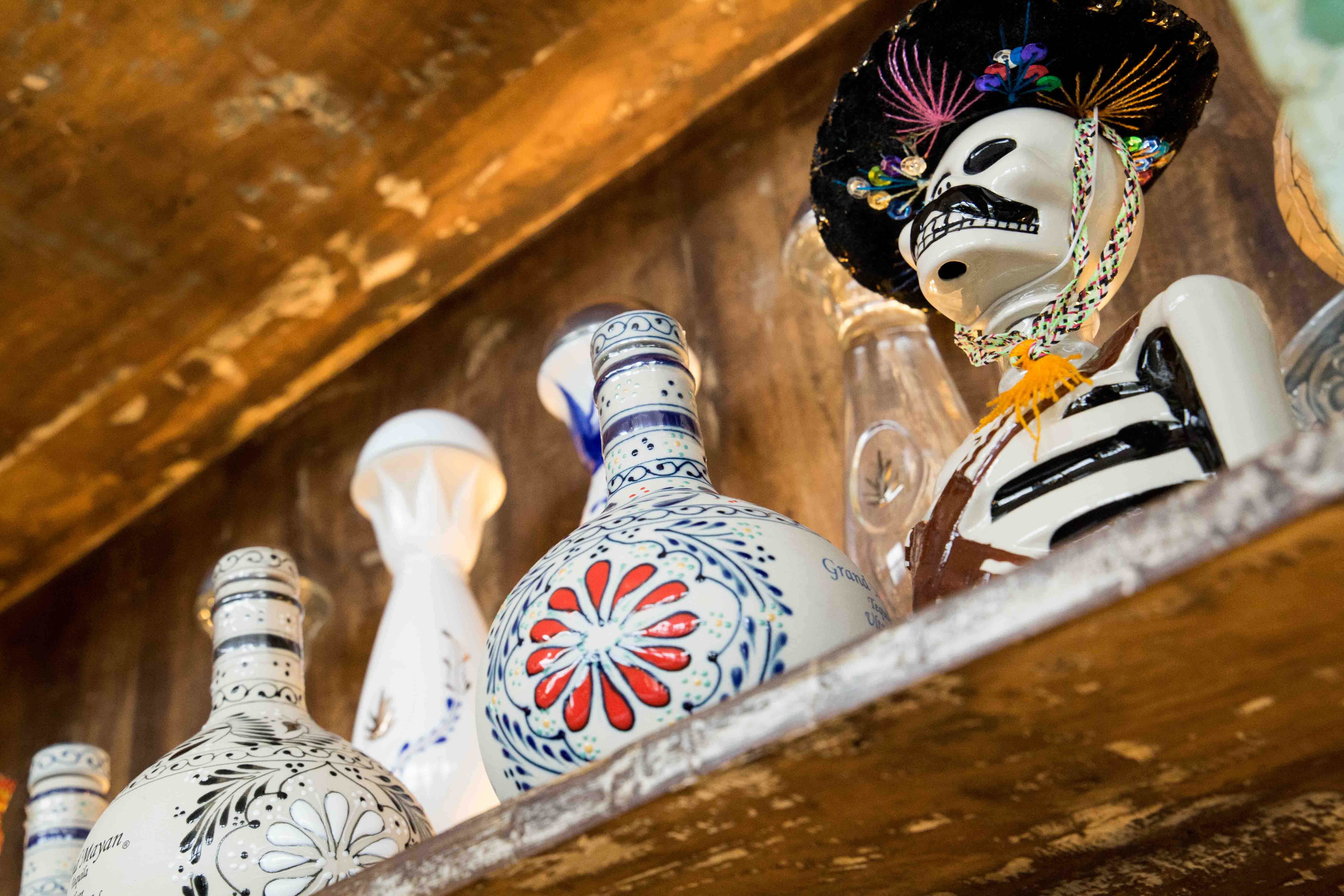 Decorated ceramic bottles of alcohol are lined up on an aged wooden shelf. One is shaped like a skeleton wearing a sombrero.