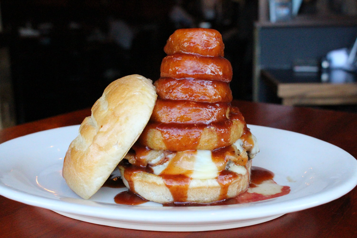 A burger sits on a white plate, its top bun leaning up against it. It's topped with a stack of five thick onion rings that are drenched in barbecue sauce.