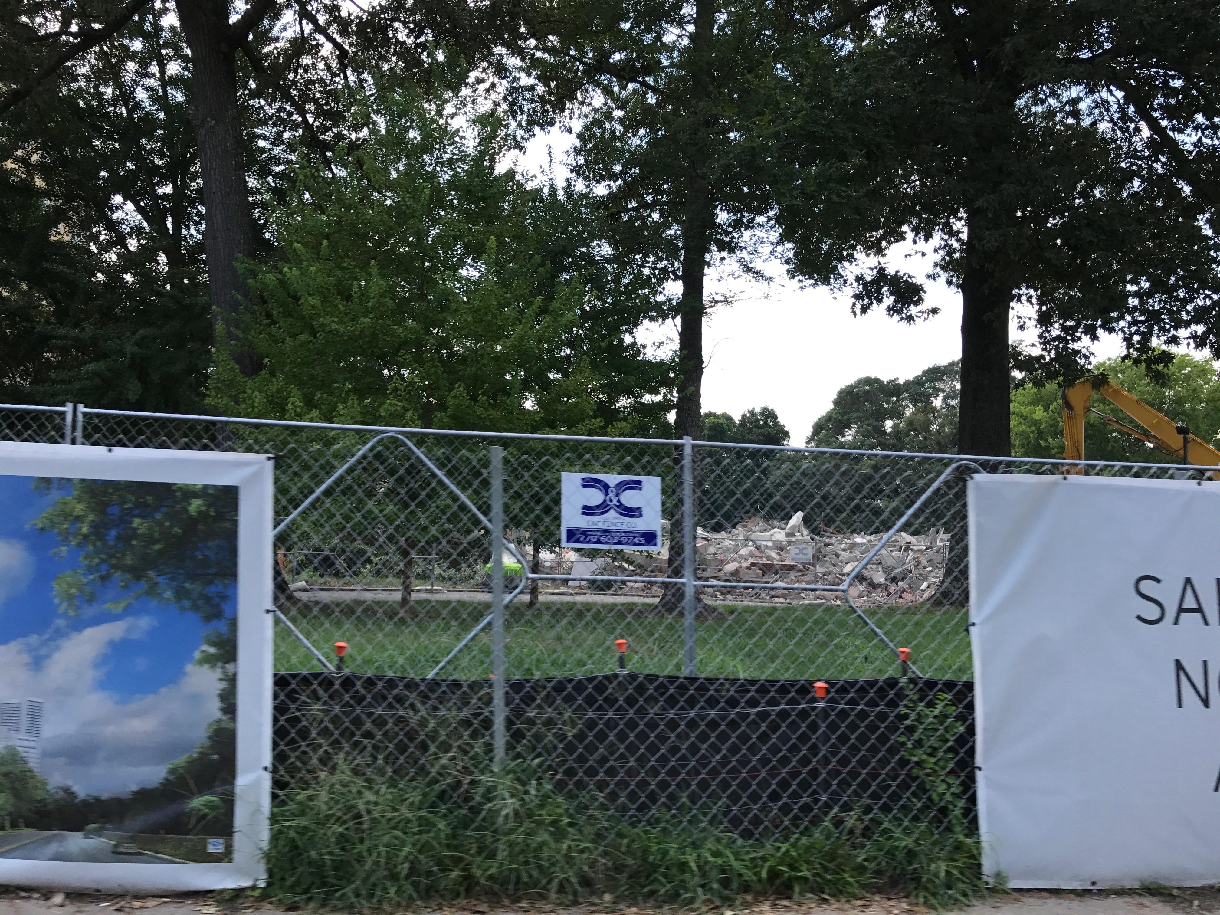 A pile of concrete, seen through a construction fence.