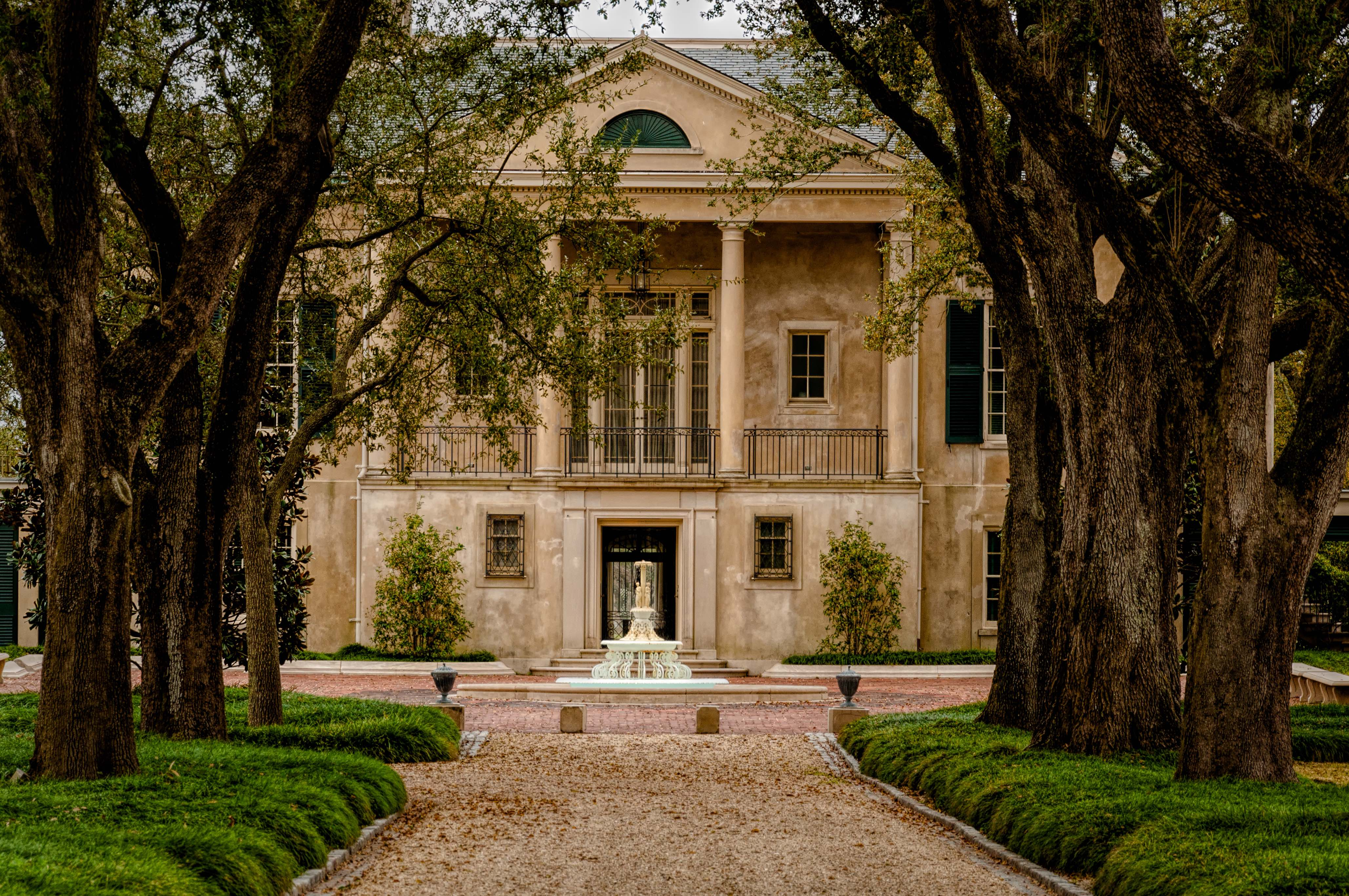 A large historic home in New Orleans that has a path leading up to its entrance through trees.