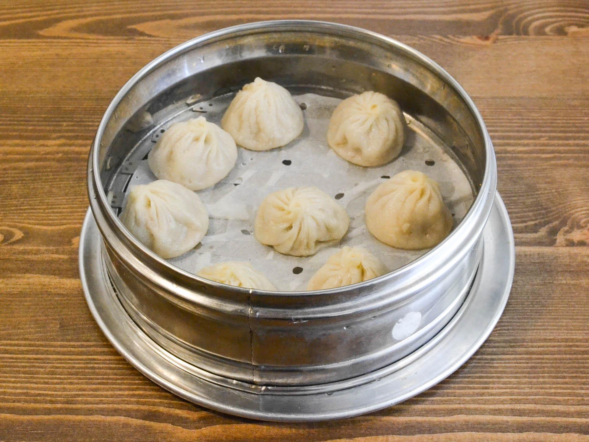 xiao long bao dumplings in a metal tin on a wooden table.