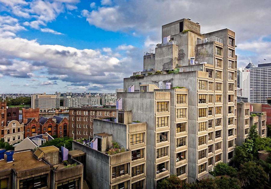 Concrete apartment block set among cityscape.