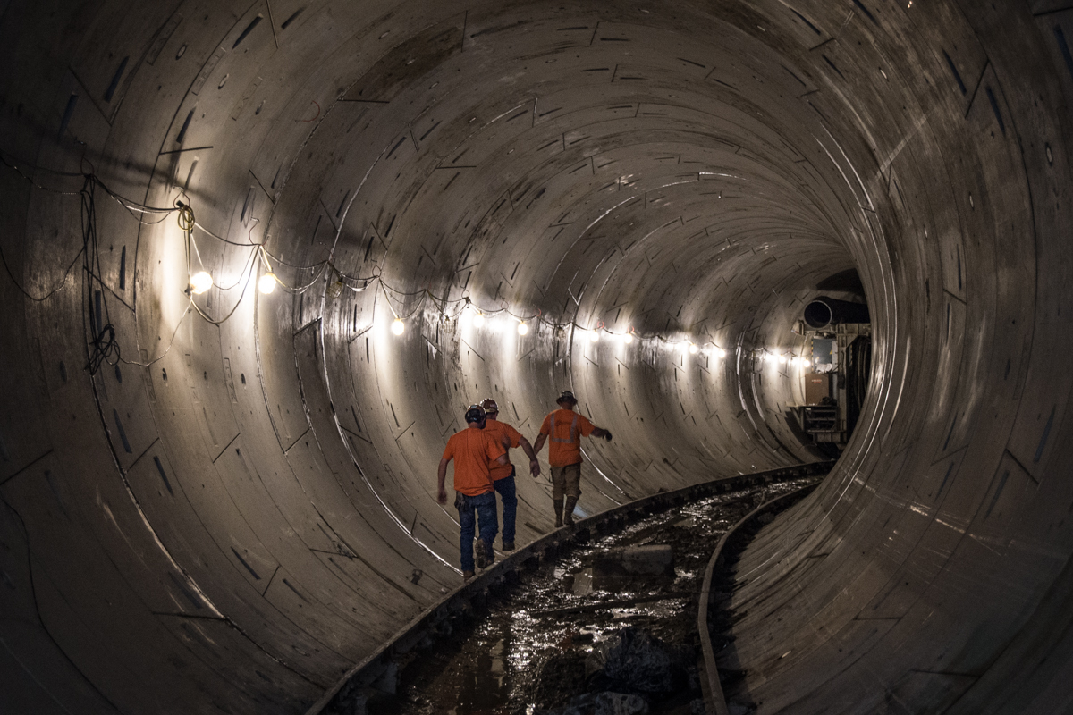 Workers in hardhats and vests walking through a dark subway tunnel with flashlights.